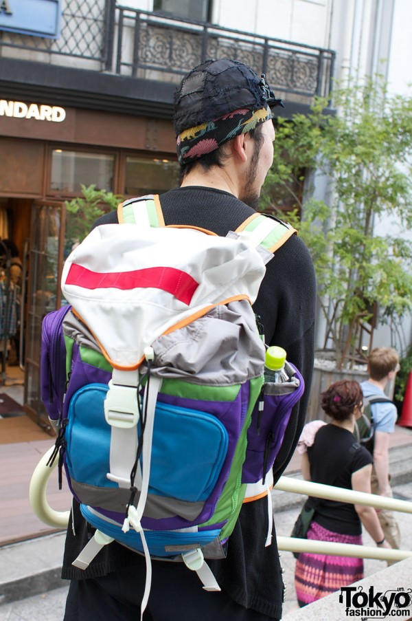 Brightly colored backpack and black patchwork hat