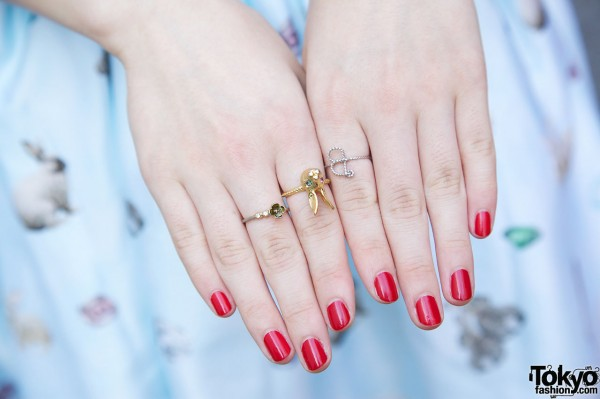 Red nail polish & delicate rings
