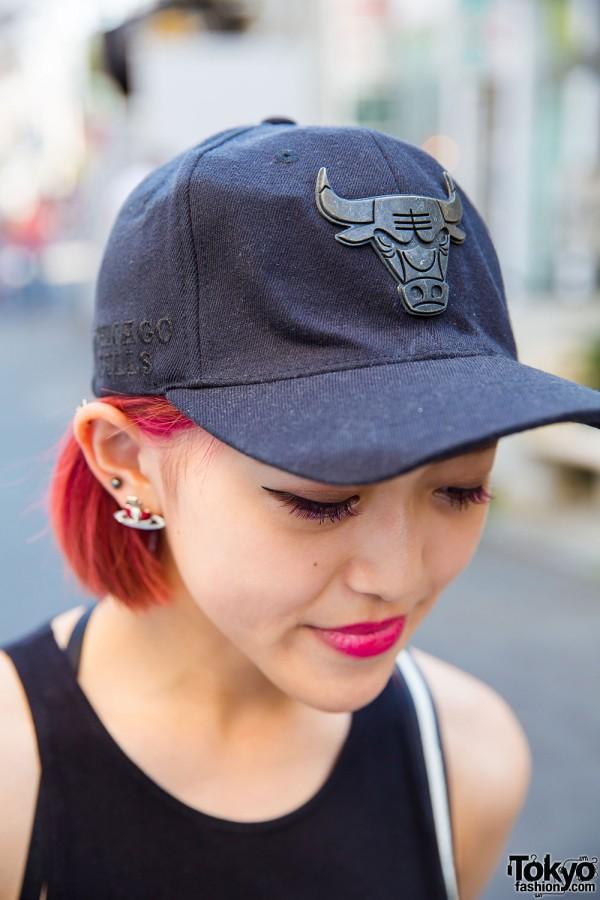 Chicago Bulls cap, red hair, and Vivienne Westwood earrings