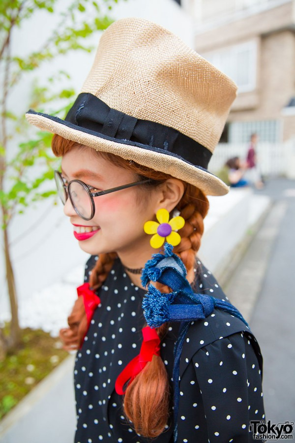 Override top hat, flower earrings, oversized glasses and twin braids with red ribbons