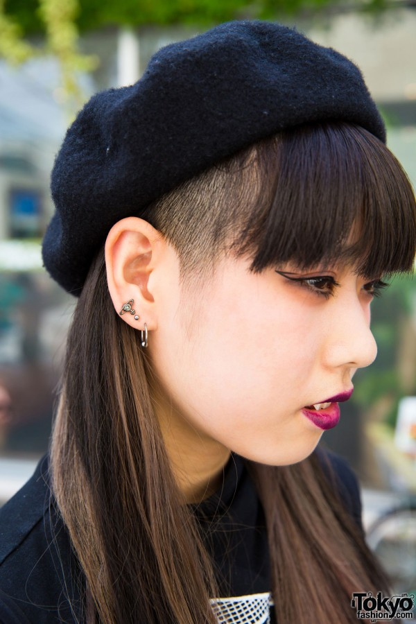 Black beret, partially shaved hair and multiple earrings