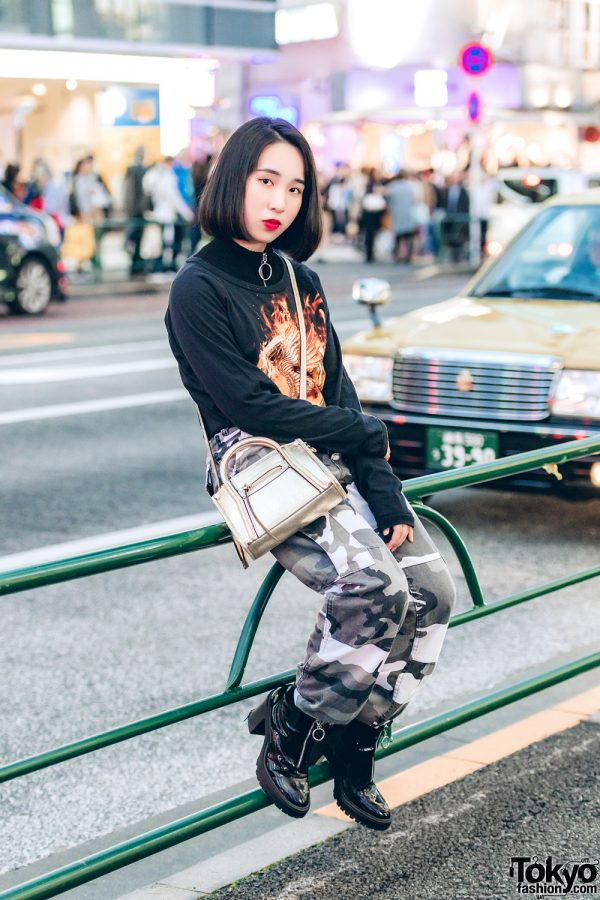Tough-Chic Streetwear w/ Graphic Sweatshirt, Camouflage Pants & Black Leather Boots