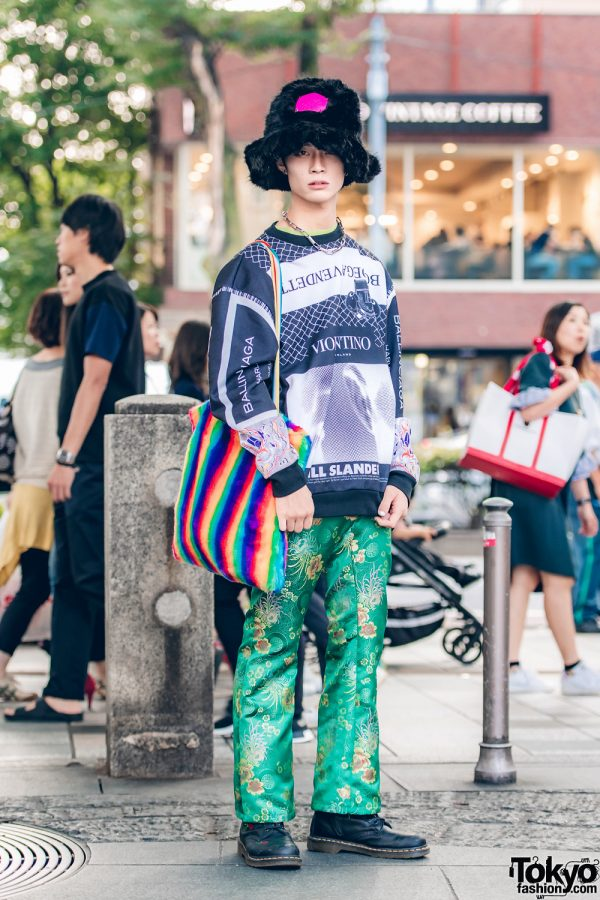 Harajuku Guy in Faux Fur Hat, Graphic Top, Floral Pants, & Rainbow Striped Bag