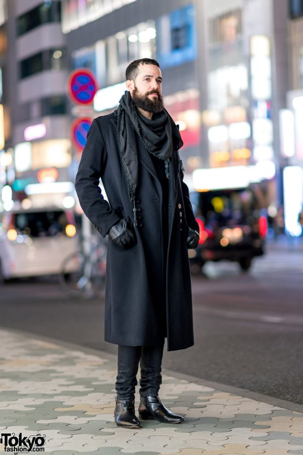 All Black Tokyo Street Style w/ Long Coat, Skirt Over Skinny Pants, Pom Pom Scarf, Leather Gloves & Pointy Boots
