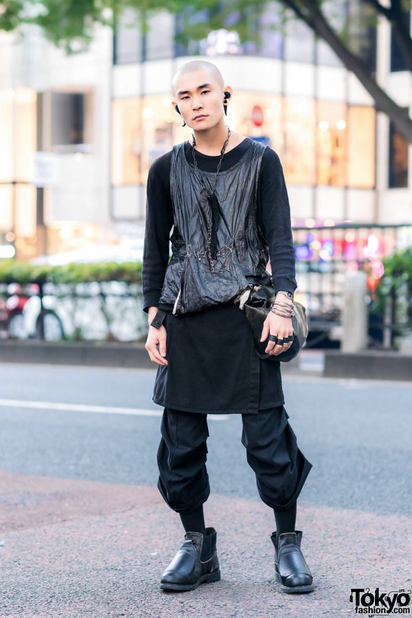All Black Layered Harajuku Streetwear Style w/ Shaved Head, Horn Earrings, Shiny Tank , Skirt Over Cropped Pants, Leather Waist Bag & Chelsea Boots