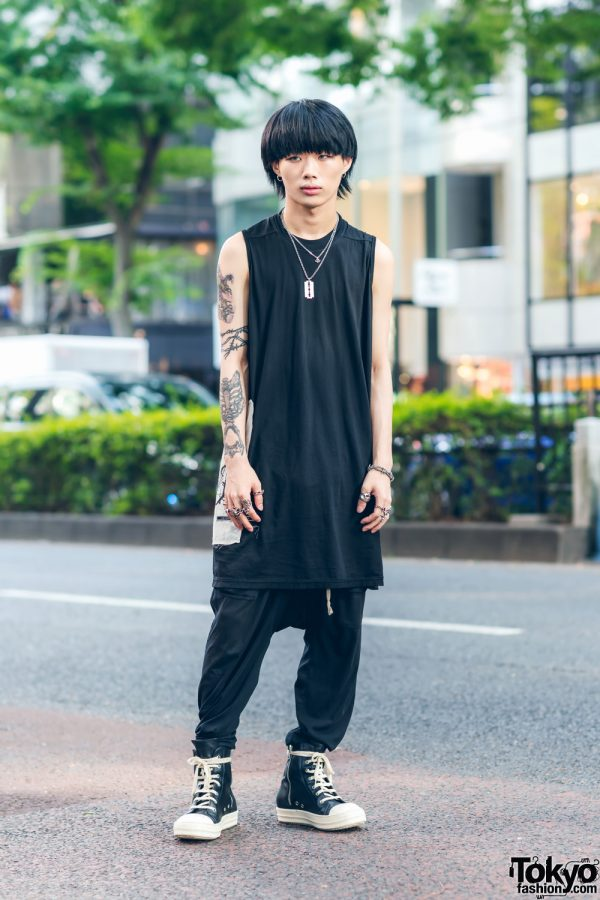 Rick Owens Monochrome Streetwear Style w/ Arm Tattoos, I'm Praying To The Aliens Long Shirt, Loose Pants, Tokyo Human Experiments Rings & High Top Sneakers