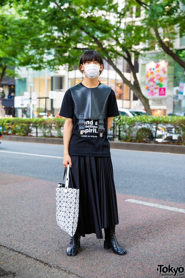 Tokyo Comme des Garcons Street Style w/ White Face Mask, Leather Half Vest, Statement Shirt, Pleated Skirt, Issey Miyake Bao Bao Bag & Maison Margiela Tabi Boots