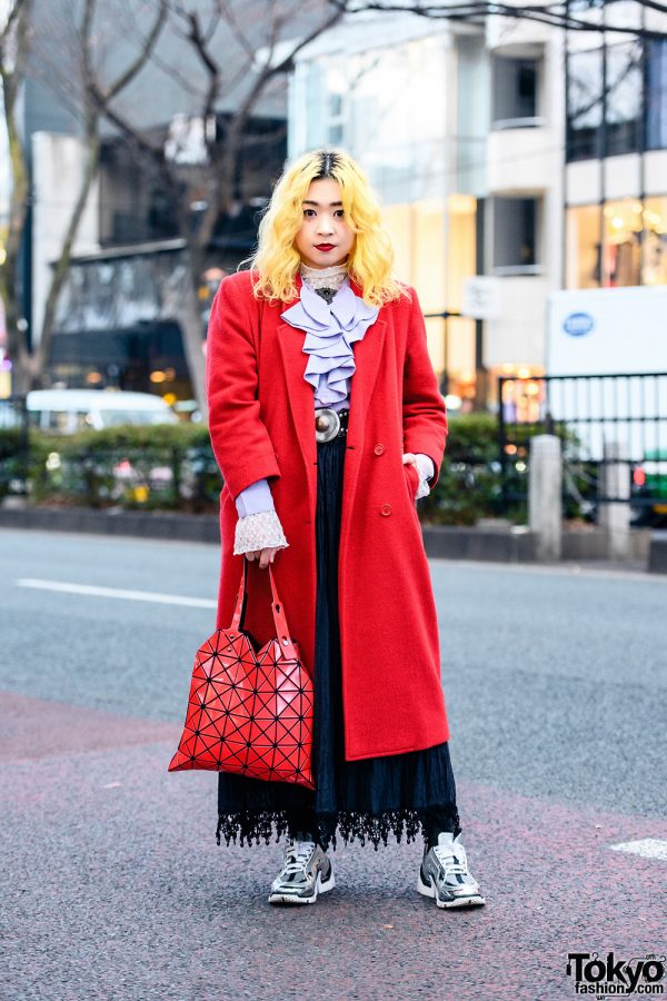 Sushi Shop Staffer Red Jacket Street Style w/ Yellow Hair, Resale Ruffled Blouse, Pierre Hardy Sneakers, Bao Bao Issey Miyake Bag, Studded Leather Belt & Ornate Brooch