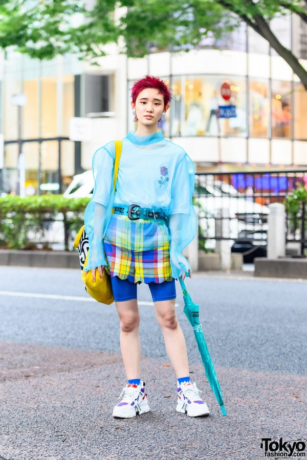 Model in Teal and Yellow Sheer Fashion w/ Pink Bob Hairstyle, Dew E Dew E Sheer Top, Aymmy In The Batty Checkered Scalloped Hem Shorts, Little Sunny Bite Tote, Jaynise Sneakers, Clear Belt, Clear Umbrella & Heart Earrings