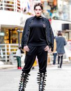 Photographer in All-Black Harajuku Street Style w/ Evangelion Tee & Demonia Damned Buckle Boots