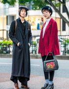 Japanese Duo in Long Coat, Asymmetrical Skirt, Corduroy Jacket w/ Badges, Suede Satchel Backpack, Newsboy Caps & Floral Applique Handbag
